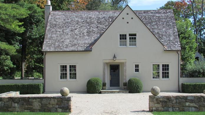 Beautiful European style cottage exterior painted #StonyGround by Farrow & Ball. Front door is #HagueBlue.